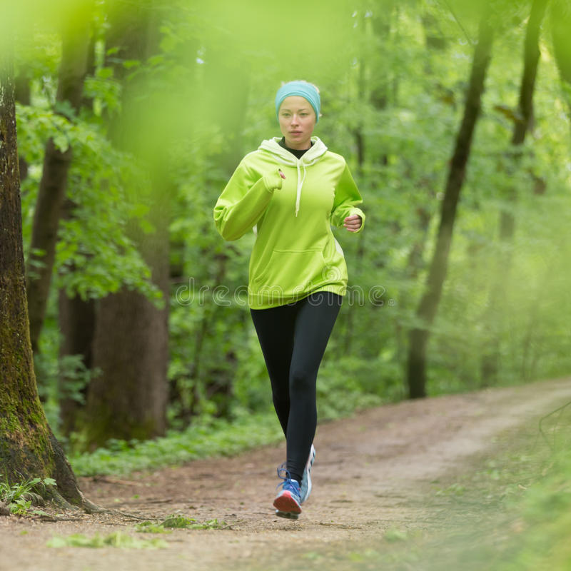 Sporty young female runner in the forest. Sporty young female runner in forest. Running woman. Female runner during outdoor workout in nature. Fitness model royalty free stock photo