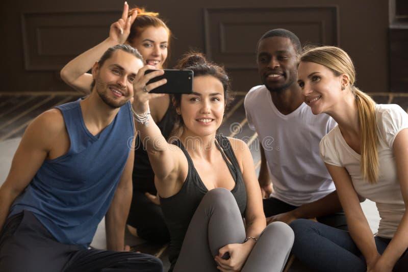 Multi-ethnic sporty people having fun taking group selfie in gym stock image