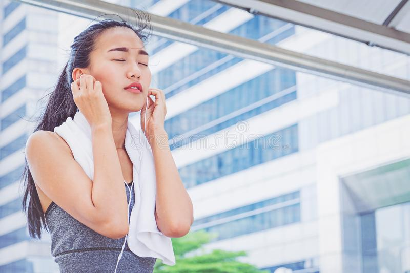 Sporty young fitness girl running and listening music in the cit royalty free stock photos