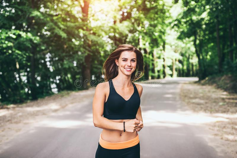 Young fitness girl running and listening music in the park stock photos