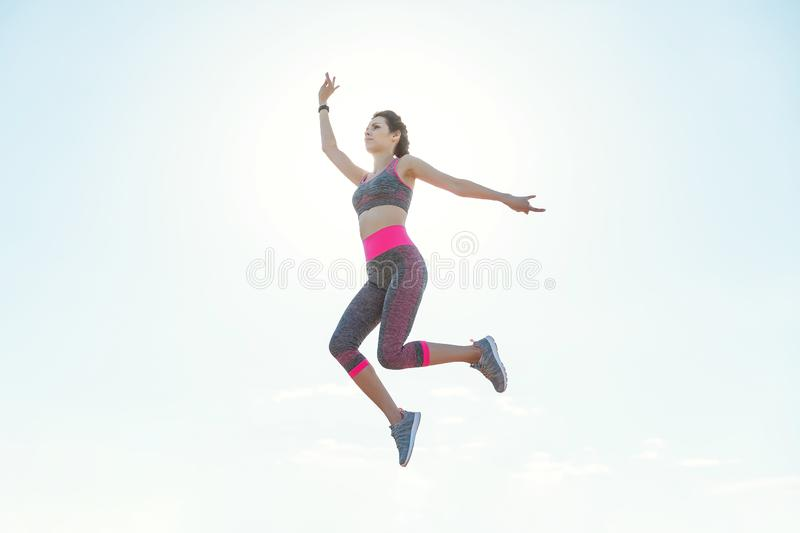Sporty young girl in the morning on pier in jump, practicing yoga. Woman do gymnastics outdoors. Health and Yoga Concept royalty free stock photo