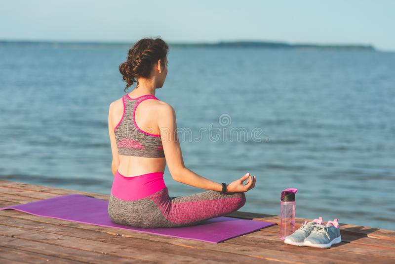 Sporty young girl in the morning on seashore, practicing yoga. Woman do gymnastics outdoor. Health and Yoga Concept stock photos