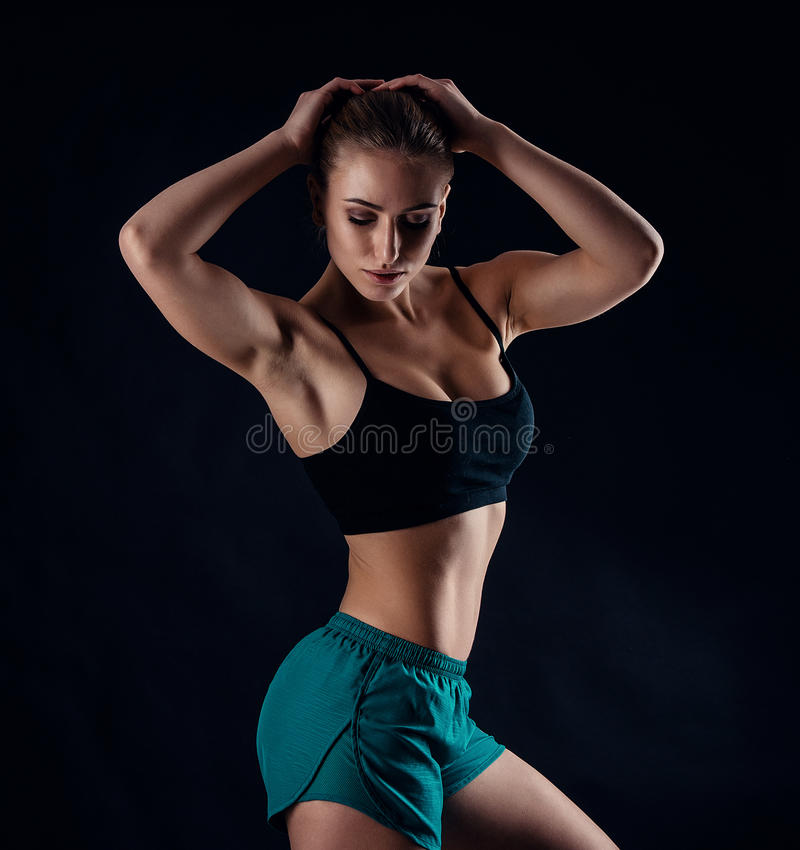 Sporty young girl in sportswear showing muscles on black background. Tanned young athletic woman. A great sport female body. Sporty young girl in sportswear royalty free stock photos