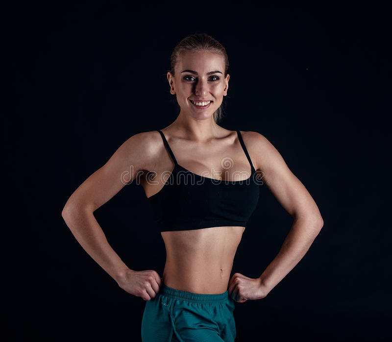 Sporty young girl in sportswear showing muscles on black background. Tanned young athletic woman. A great sport female body. Sporty young girl in sportswear stock images