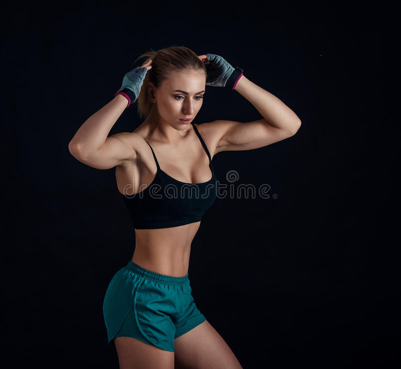 Sporty young girl in sportswear showing muscles on black background. Tanned young athletic woman. A great sport female body. Sporty young girl in sportswear royalty free stock photo