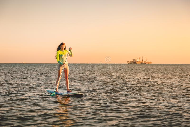 Sporty young girl stand up paddle surfing with beautiful sunset colors royalty free stock photos