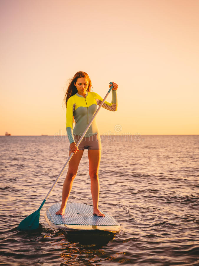 Sporty young girl stand up paddle surfing with beautiful sunset or sunrise colors royalty free stock images