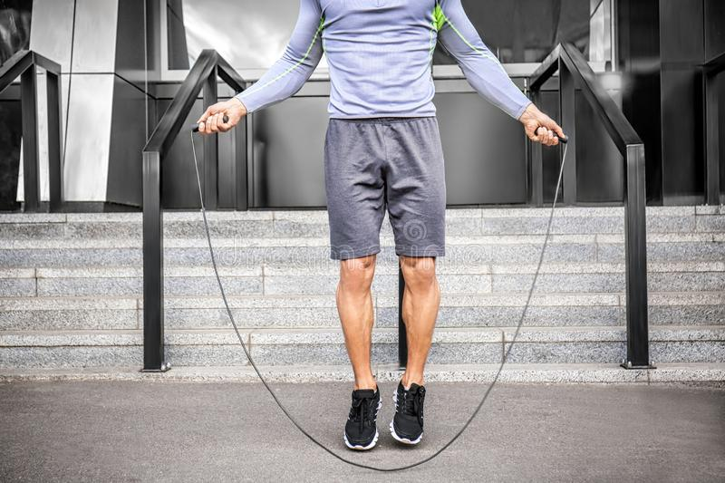 Sporty young man jumping rope outdoors stock photos
