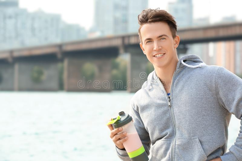 Sporty young man with protein shake, stock photography