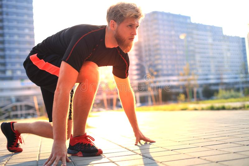 Sporty young man in start position outdoor at sunset or sunrise. Sporty young man in start position outdoor at sunset or sunrise royalty free stock images