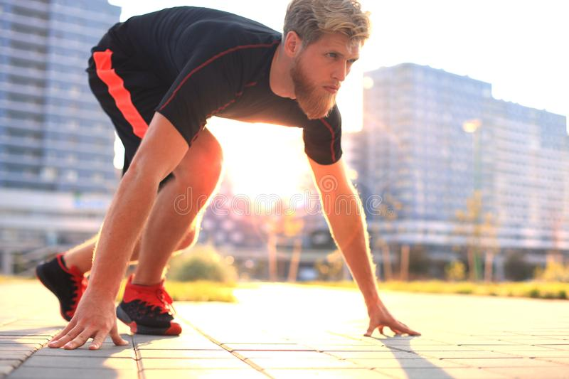 Sporty young man in start position outdoor at sunset or sunrise. Sporty young man in start position outdoor at sunset or sunrise stock photo