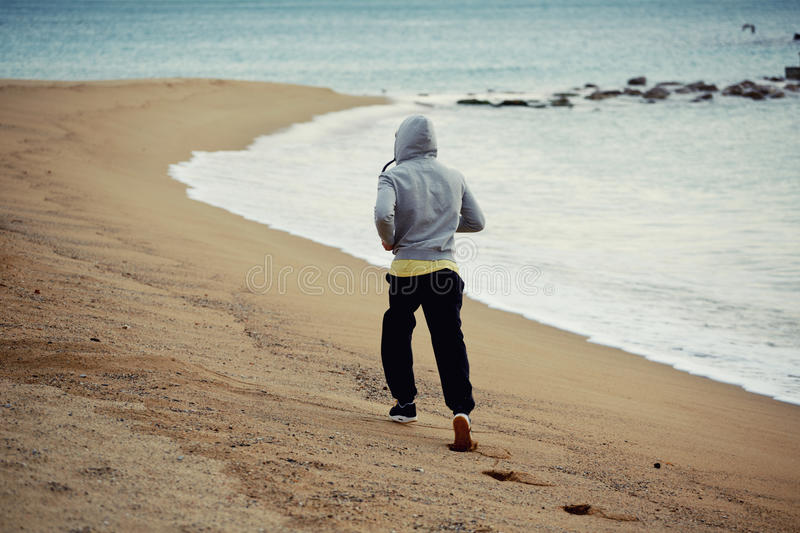 Sporty young man working out at early morning while run along the seashore over wet sand royalty free stock images