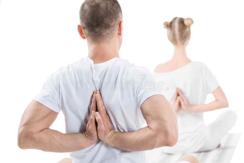 Sporty young people sitting in lotus position with namaste mudra sign stock photography