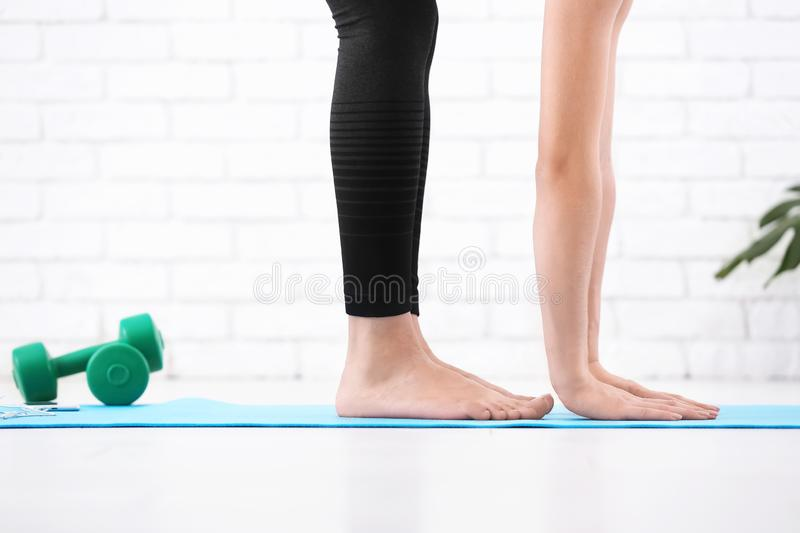 Sporty young woman doing exercise on mat indoors stock image