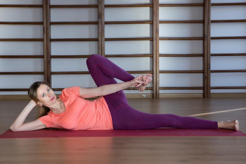 Sporty young woman doing yoga practice - concept of healthy life and natural balance between body and mental development. Relaxation and meditation royalty free stock photography