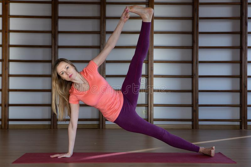 Sporty young woman doing yoga practice - concept of healthy life and natural balance between body and mental development. Relaxation and meditation stock image