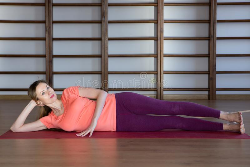 Sporty young woman doing yoga practice - concept of healthy life and natural balance between body and mental development. Relaxation and meditation stock photography