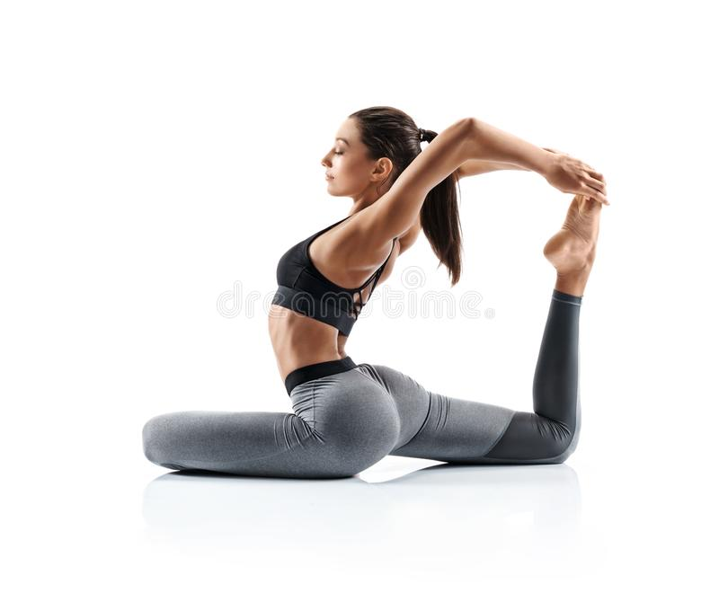 Sporty young woman doing yoga practice isolated on white background. royalty free stock photo