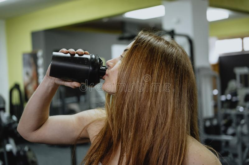 Sporty young woman drinking water while working out in gym stock photo