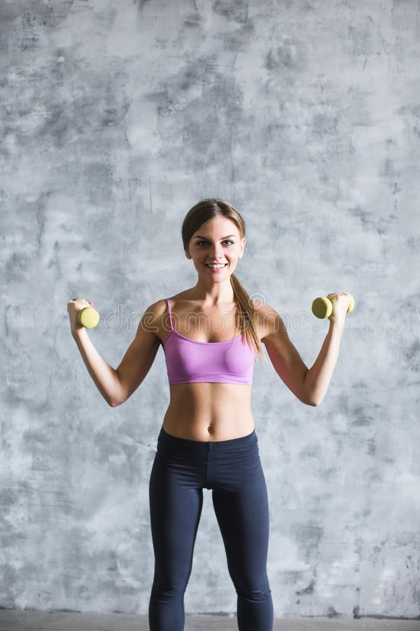 Sporty young woman with dumbbells on gray background. royalty free stock images