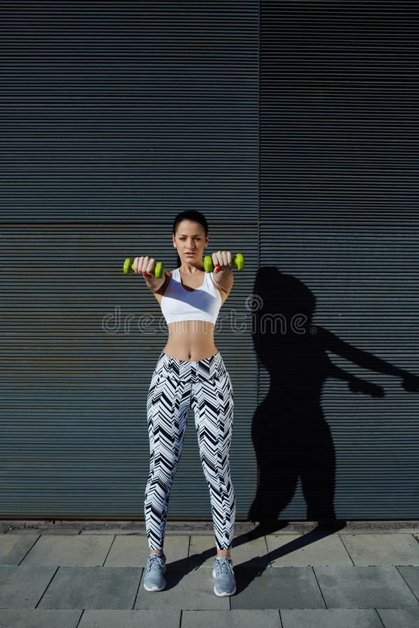 Sporty young woman holding weights standing on black wall background at sunset. Athletic woman holding weights with hands up at her front getting arms in great stock photography