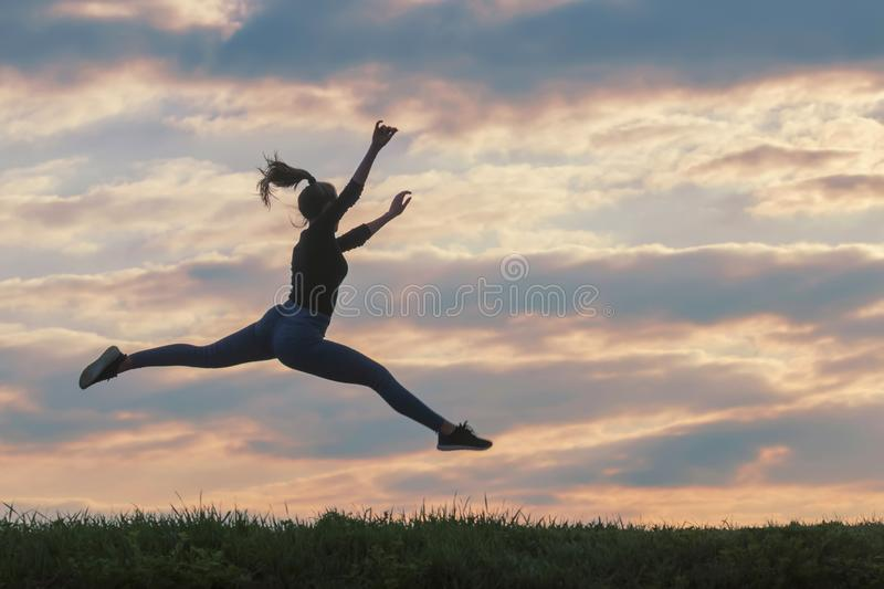Sporty young woman jumping outdoor morning clouds background, Athlete Woman jump beautiful sunrise morning workout royalty free stock photo