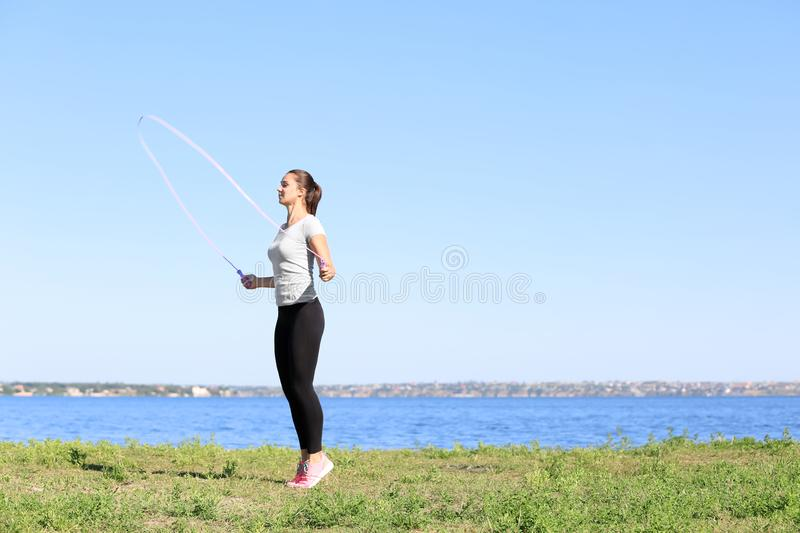 Sporty young woman jumping rope outdoors royalty free stock images