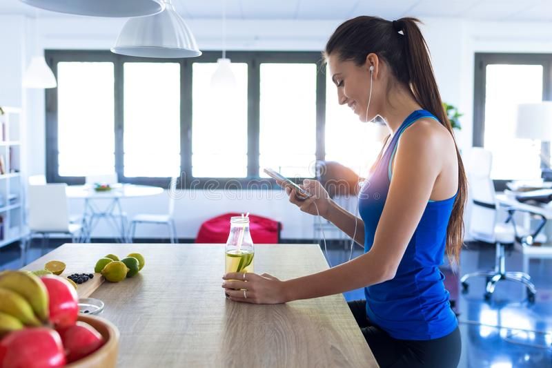 Sporty young woman listening to music with mobile phone after training in the kitchen at home stock images