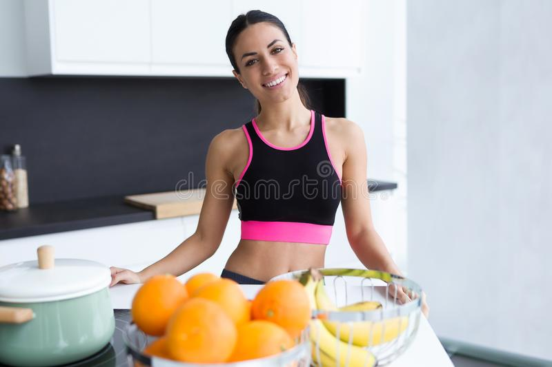 Sporty young woman looking at camera while posing in the kitchen at home stock image