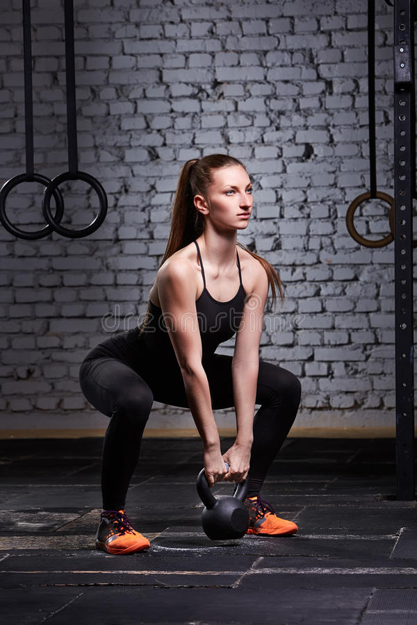 Sporty young woman with muscular body doing crossfit workout with kettlebell against brick wall. royalty free stock image