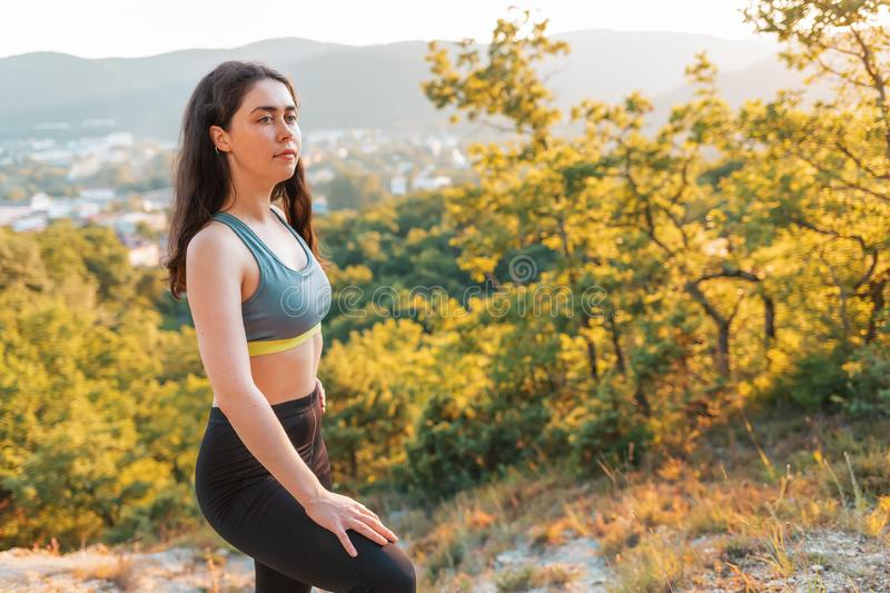 Sporty young woman resting during training. In the background plants and views of the settlements. The concept of sport, healthy stock photo
