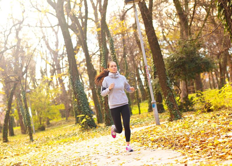Sporty young woman running in the park and listening to music. royalty free stock images