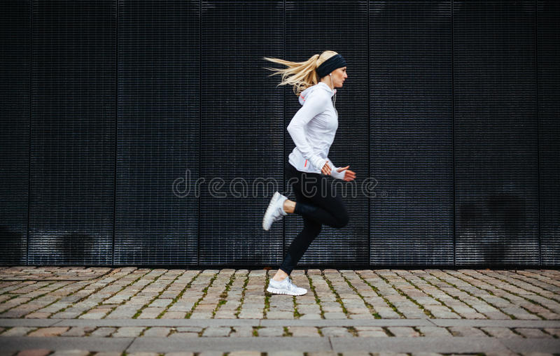 Sporty young woman running on sidewalk in morning. Side view of sporty young woman running on sidewalk in morning. Health conscious concept with copy space stock images