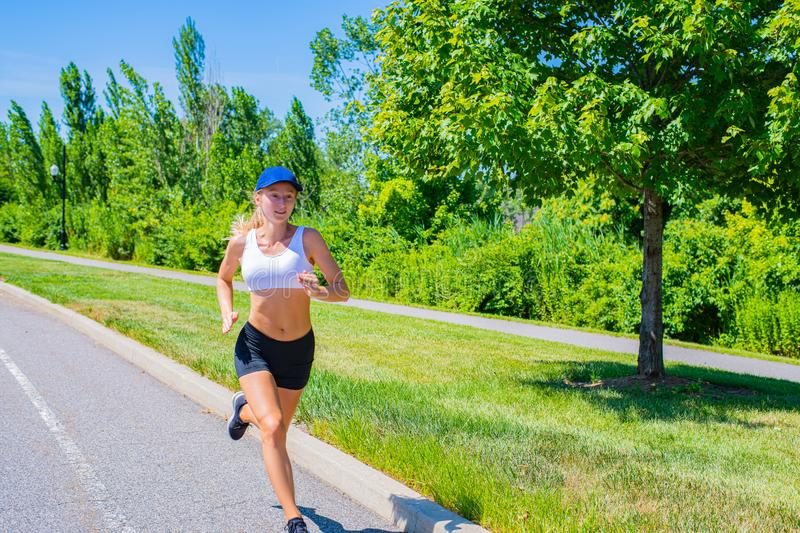 Sporty woman in sportswear trail running on the road. Athlete girl is jogging in the park royalty free stock photo