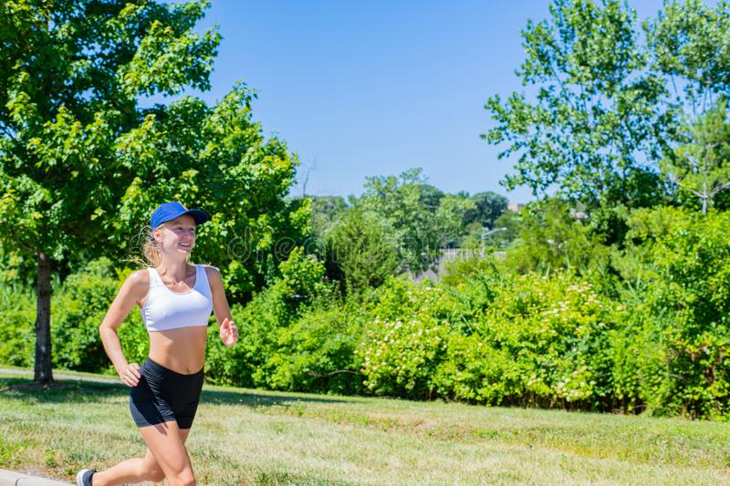 Sporty woman in sportswear trail running on the road. Athlete girl is jogging in the park stock photography