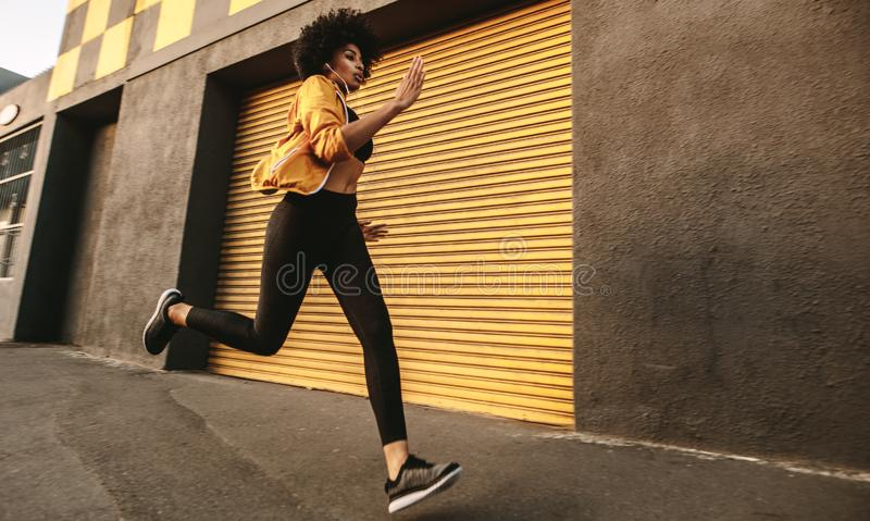 Sporty young woman sprinting outdoors stock photos
