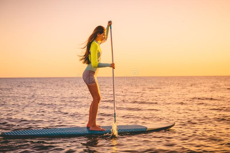 Sporty young woman at stand up paddle board with beautiful sunset colors royalty free stock photography