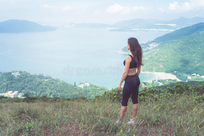 Sporty young woman standing on hill admiring the view of sea and green mountains in sunlight royalty free stock photos