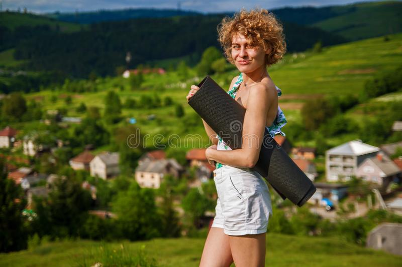 Sporty young woman standing on hill admiring the view of sea and green mountains in sunlight. royalty free stock image