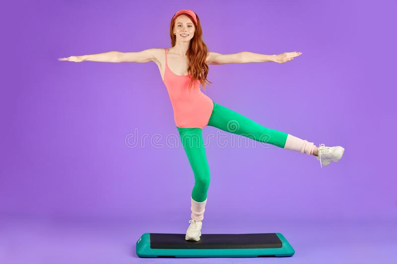 Sporty young woman standing on one leg at step deck and holding balance. Sporty young joyful red-headed woman standing on one leg at step deck and holding stock images