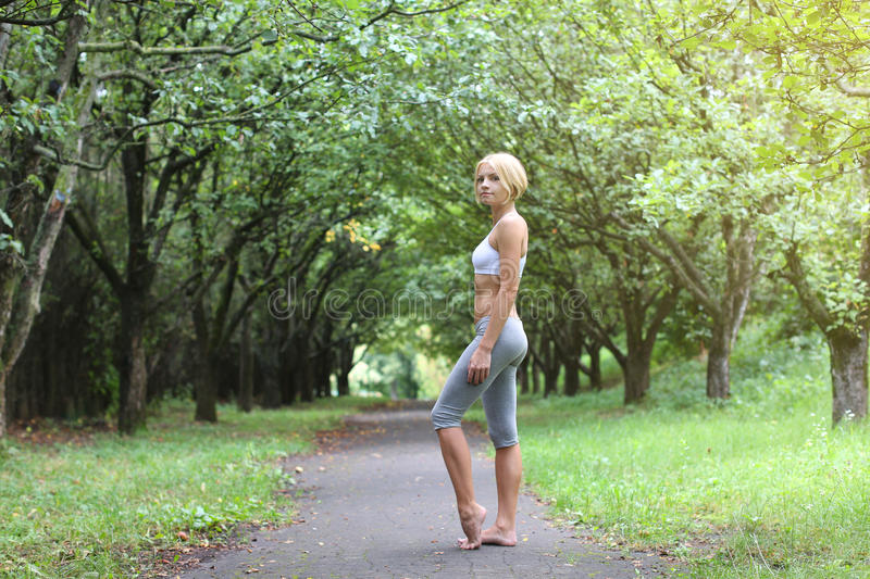 Sporty young woman stay barefoot in park. Yoga woman. Young fit bootless woman in the morning park. Foot free royalty free stock photos