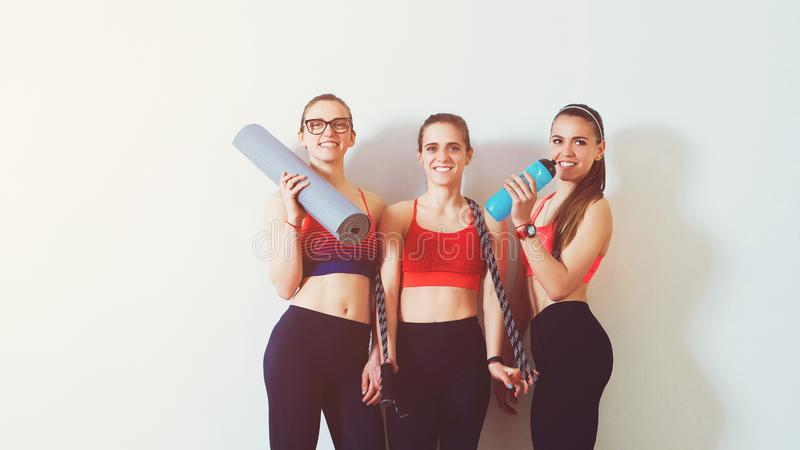 Sporty young women standing against wall. Sports background. Three fitness girls in gym after workout. Copy space. Females in spor royalty free stock images