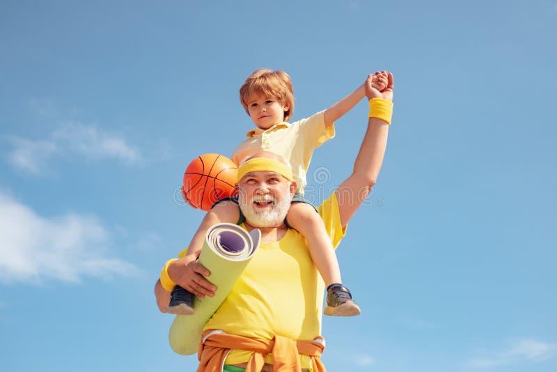 Sportyoga en fitness Grootvader die de Rit van de Kleinzoon op in Park teruggeeft Opa en kleinzoon het bevlekken Actieve gezond royalty-vrije stock afbeeldingen