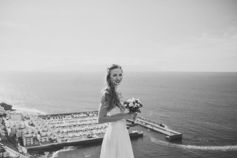 Sposa abbastanza felice in vestito bianco con il mazzo di nozze fotografia stock