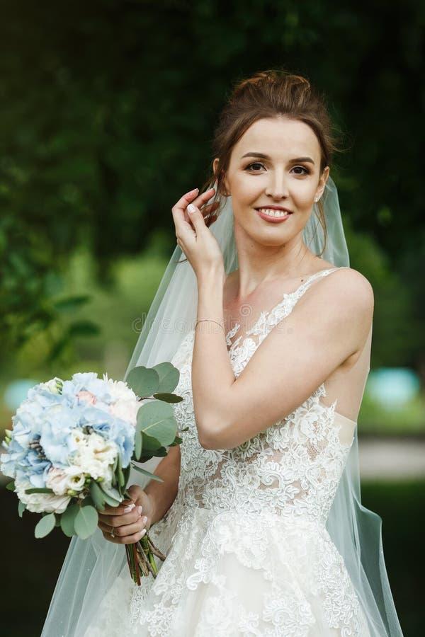 Sposa abbastanza felice in vestito di lusso con il mazzo delle rose fotografie stock