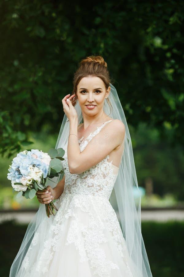 Sposa abbastanza felice in vestito di lusso con il mazzo delle rose immagini stock libere da diritti