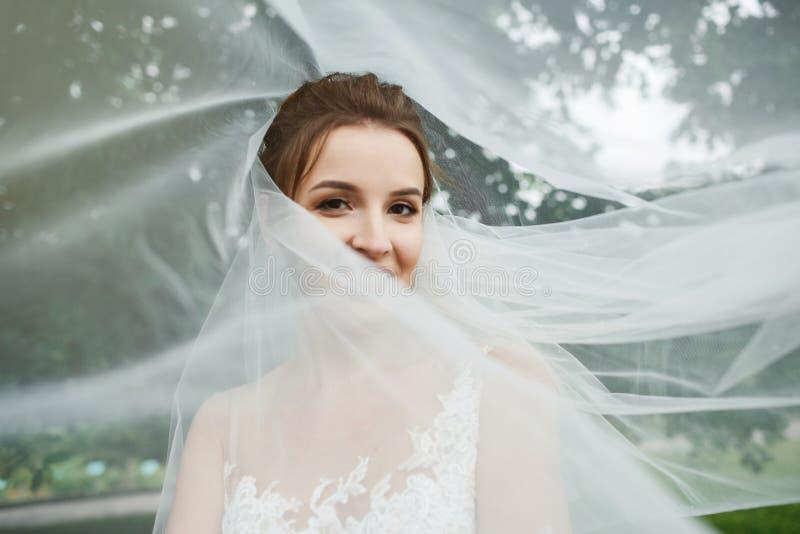 Sposa abbastanza felice in vestito di lusso con il mazzo delle rose fotografia stock