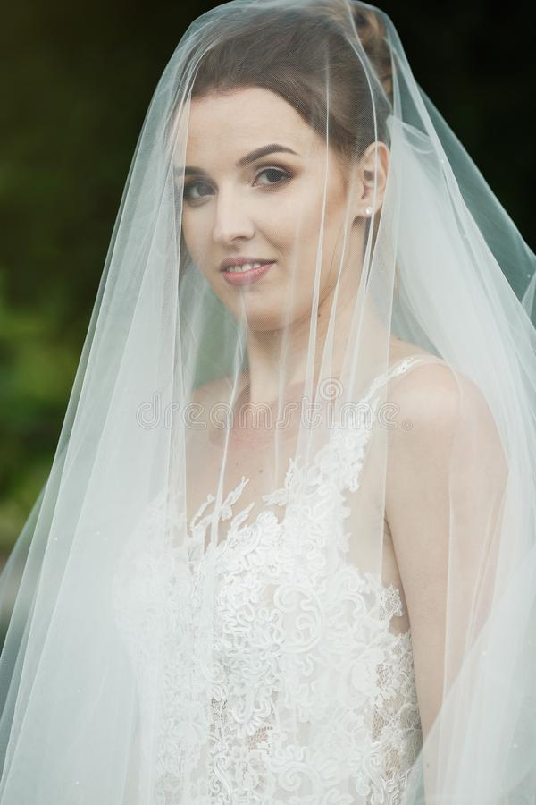Sposa abbastanza felice in vestito di lusso con il mazzo delle rose immagini stock