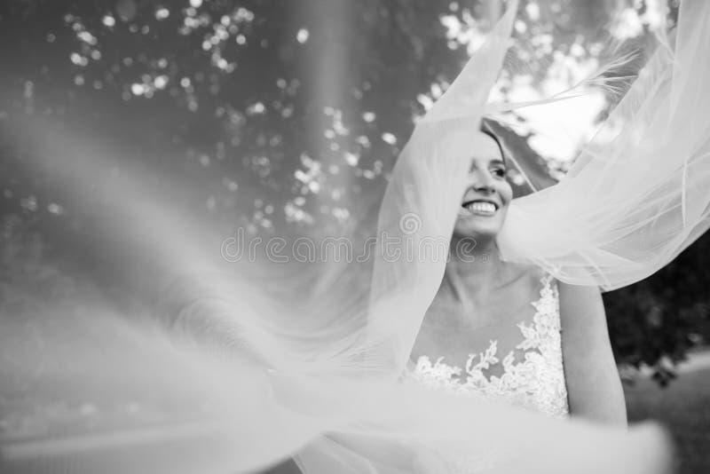 Sposa abbastanza felice in vestito di lusso con il mazzo delle rose immagine stock libera da diritti