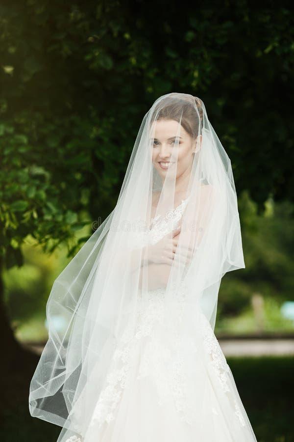 Sposa abbastanza felice in vestito di lusso con il mazzo delle rose fotografia stock libera da diritti